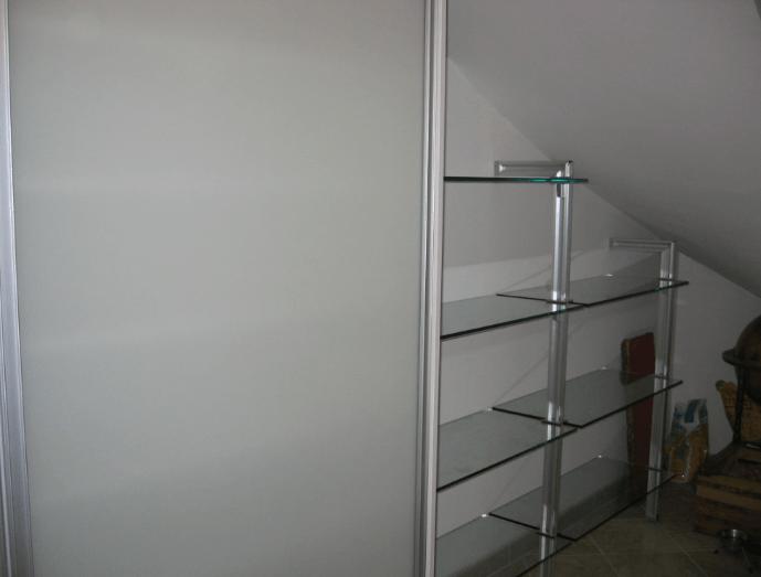 odprte steklene police pod poševnim stropom